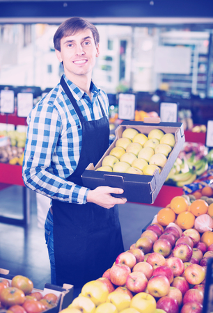 Portrait of young worker offering fruits in grocery and smiling Stock Photo