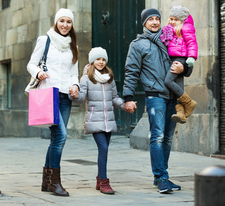Winter portrait of happy young smiling adults with little daughters. Focus on man Stock Photo