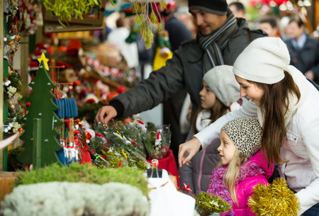 Cheerful young parents with two little children buying flower and coniferous decorations for Christmas. Focus on woman