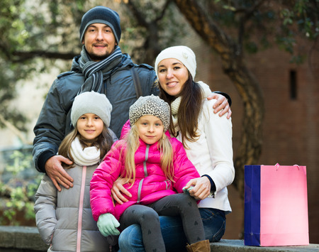 Happy young family with two children posing outdoors in winter. Focus on blonde girl