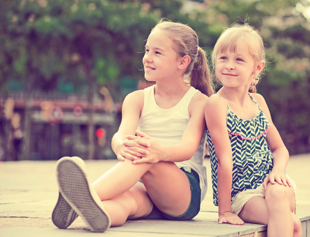 5s: Two small happy sisters sitting outdoors, looking into distance