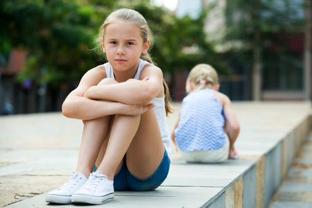 Two offended little girls not talking to each other after quarrel outdoors