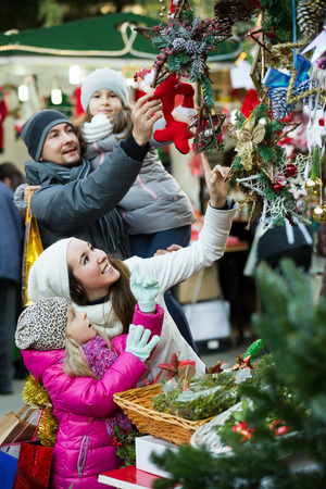 Family of four choosing floral christmas decorations at market. Focus on woman and girl