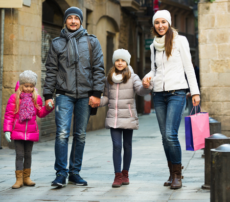 Winter portrait of young cheerful smiling adults with little daughters. Focus on girl
