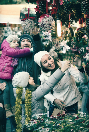 Ordinary family with little girls standing at coniferous Christmas souvenirs counter at fair. Focus on women and child in gray clothes
