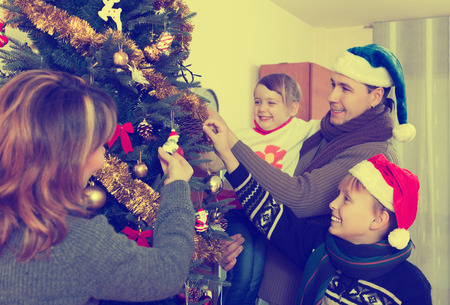 living room: Family of four people decorating Christmas tree in the living room at home Stock Photo