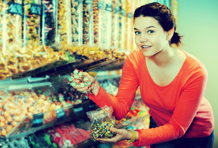 Happy woman posing to photographer picking different candies with  scoop in  cellophane bag