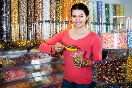 company: Portrait of young smiling girl choosing sweets for gift in candies shop Stock Photo