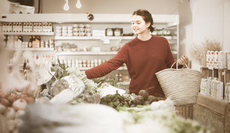 Portrait of young female customer looking cauliflower  in grocery