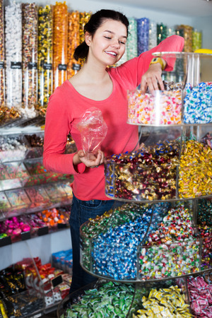 Portrait of smiling girl choosing candies for gift in sweets shop