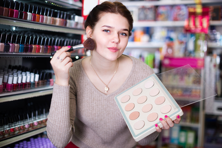 Customer girl is searching for reliable compact powder in cosmetics shop.