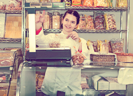 company: Diligent friendly smiling girl in uniform  selling candied fruits and nuts