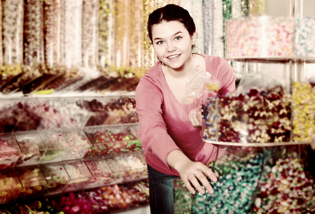 company: Woman in store is picking up candies by hands into package. Stock Photo