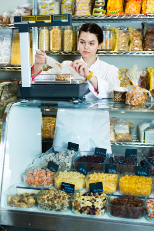 company: Positive  friendly smiling girl in uniform  selling candied fruits and nuts Stock Photo