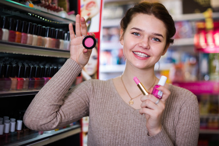 Young female customer looking for make-up items in cosmetics shop