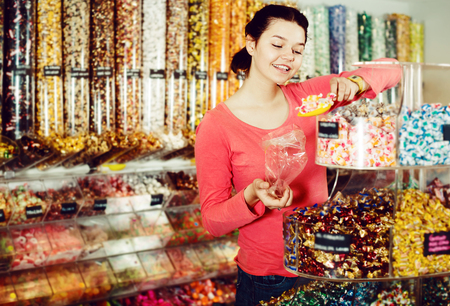 company: Attractive young woman posing to photographer picking different candies with  scoop in  cellophane bag