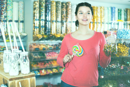 company: Young smiling girl choosing candies for gift in sweets shop
