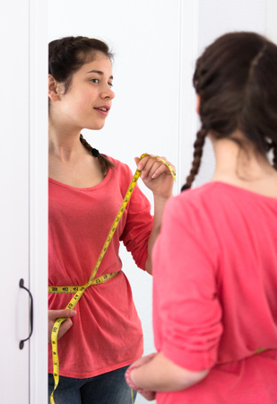 Smiling young girl measuring waist after weight loss at home