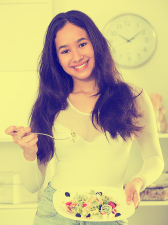 Cheerful young woman have lunch at home eating freshness salad