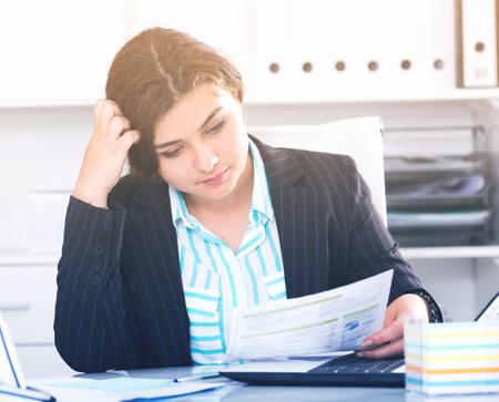 potěšen: Žena stážek čte dokumenty o transakci v kanceláři. Reklamní fotografie