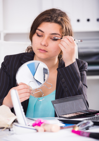 company: Woman 19-24 years old is making makeup before meeting in office. Stock Photo