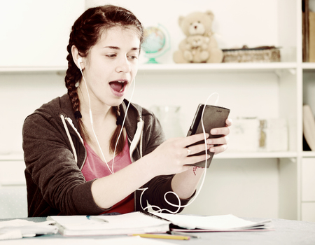 Smiling girl texting with her phone and listening to music at home Stock Photo