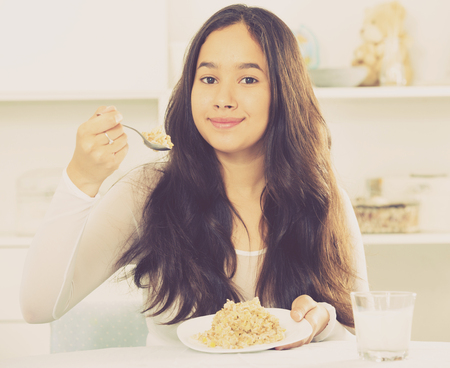 Positive young female eating cereals witn spoon sitting at home