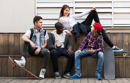 company: happy spanish girl and three boys hanging out outdoors and discussing something Stock Photo