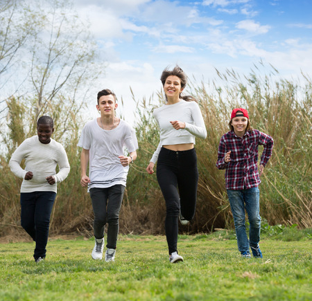 company: Portrait of four friends running on countryside field in sunny day