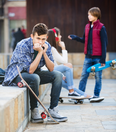 Envy male teen sitting aside of girlfriend talking with boy in the city Stock Photo