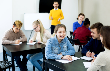 onderwijs: Friedly classmates and teacher working in groups to complete task during class Stockfoto