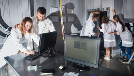 Group of adults in play trying to get out of escape room stylized under laboratory Stock Photo