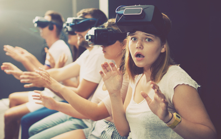 avocation: Agitated young woman experiencing with friends virtual reality Stock Photo