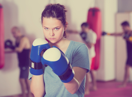concentrated sportwoman in the boxing hall practicing boxing punches during training Stock Photo