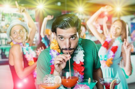 Bearded man is drinking cocktail on hawaiian party