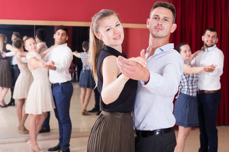 Adult dancing couples enjoying foxtrot in dance studio