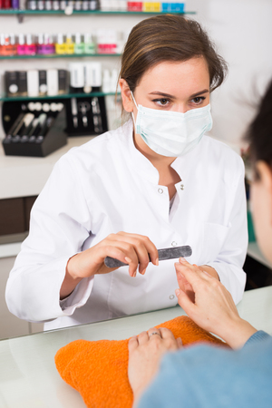 Manicure master shaping nails to female client with nail file Stock Photo