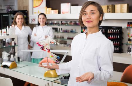 美容院でマニキュアの色を選択する女性のクライアントに提供するネイル技術者