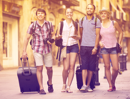 Company of positive young travelers with travel bags walking the city
