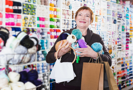 Happy woman with shopping bags using phone in needlework store Stock Photo