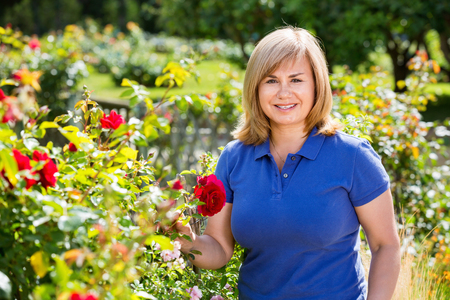 Smiling happy charming blond mature woman gardening red roses and holding horticultural tools on sunny day Stock Photo