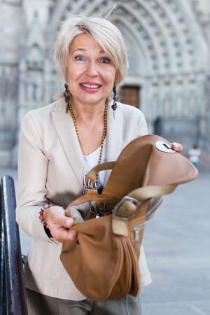 robo: Mature woman is upset because her purse was been stole from bag on the street.