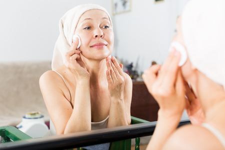 Mature woman getting face clean for beauty procedures at home Stock Photo