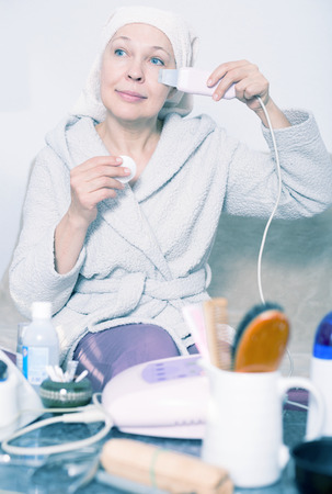 Mature woman getting face cleaned with ultrasonic device at home Stock Photo