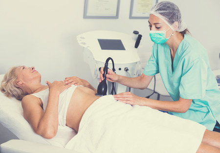 Professional cosmetician performing cryolipolyse treatment in clinic of esthetic cosmetology Stock Photo