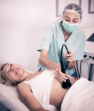 esthetics: Woman receiving innovative procedure of cryoliposuction in clinic of esthetic cosmetology Stock Photo