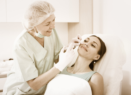 esthetics: Young woman getting injection for facial correction procedure in esthetic clinic