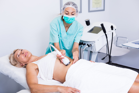Female getting cryolipolyse treatment in cosmetic cabinet