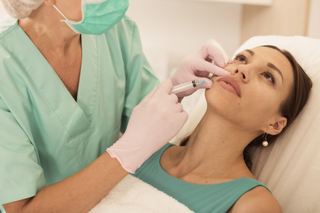 Young woman getting injection for facial correction procedure in esthetic clinic