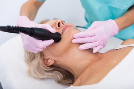 Close up of mature female getting facial cryolipolyse treatment in cosmetic cabinet Stock Photo